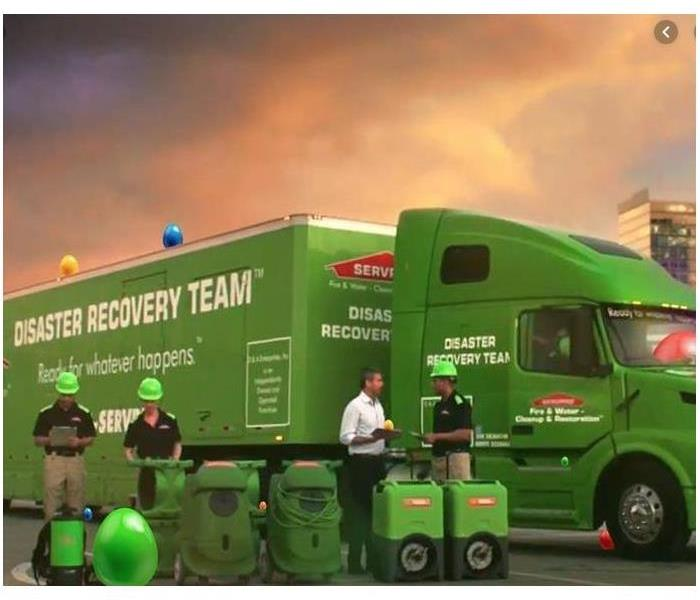 SERVPRO trucks in the background, SERVPRO equipment in the foreground, and SERVPRO staff talking to one another.