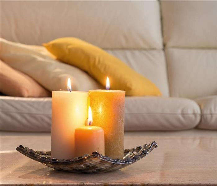 three candles lit up placed on a plate holder on a table background of a couch
